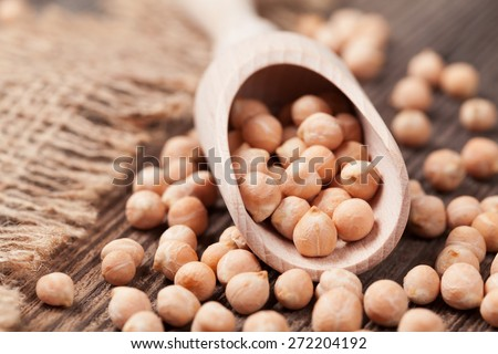Organic raw chick peas healthy protein nutrition super food in wooden spoon on dark background. Close up view - stock photo