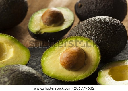 Organic Raw Green Avocados Sliced in Half - stock photo