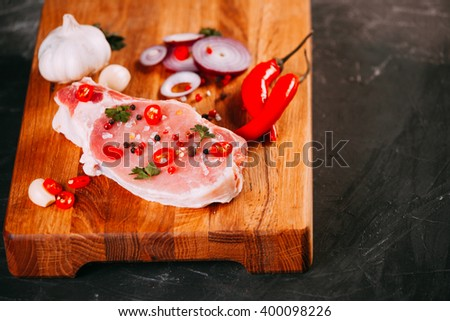 Organic raw pork meat on chopping board. Decoreted with spices, fresh garlic, chili papper and parsleys. Simple tasty food prepared for cooking. Set of products for grill, barbecue  - stock photo