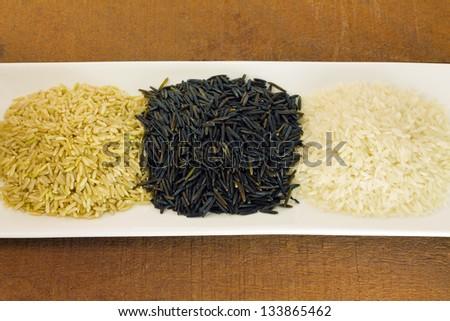 Organic raw rice. Wild rice, brown rice and white rice - stock photo