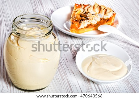 Organic Raw Sour Cream in a glass jar with piece of apricot homemade tart on plate on white background, close-up