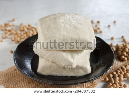 Organic Raw Soy Tofu on black plate with soy beans. - stock photo