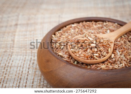 Organic rice in wooden chalice - stock photo