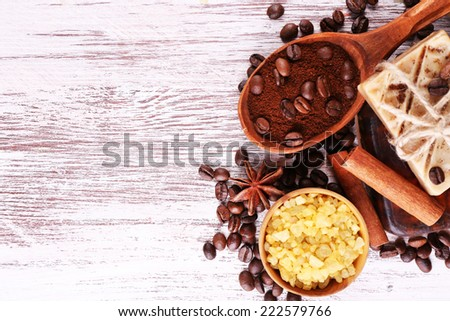 Organic soap with coffee beans, sea salt and milled coffee in wooden spoons on wicker mat, on wooden background, Coffee spa concept - stock photo