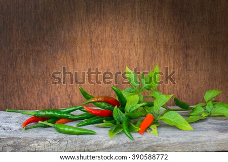 Organic Thai pepper, fresh red and green chilli on old wood background. guinea pepper ; bird pepper ; bird-chilli ; small capsicum ; chilli pepper ; tiny fiery chilli ; hot chilli - stock photo