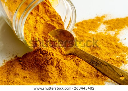 Organic turmeric (curcuma) powder in glass jar with measuring spoon on white background - stock photo