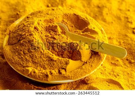 Organic turmeric (curcuma) powder in white bowl with measuring spoon - stock photo
