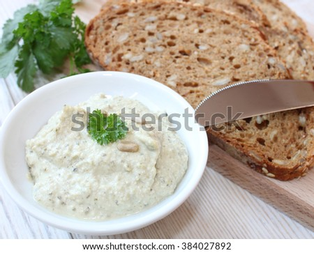 organic vegetable spread with herbs and grain bread and ingredients in the background on a wooden table - stock photo