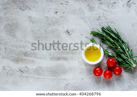 Organic vegetables cooking ingredients with rosemary, olive oil and tomatoes over grey concrete background, top view, place for text, border. Healthy lifestyle or detox diet food concept. - stock photo