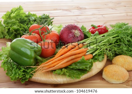 Organic vegetables in rustic setting including tomatoes on the vine, peppers, carrots, lettuce. - stock photo