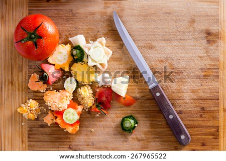 Organic Wastes from Veggies and Spices, Can be Used to Compost Garden Soil, on Top of Wooden Chopping Board with Kitchen Knife. Captured in High Angle View. - stock photo