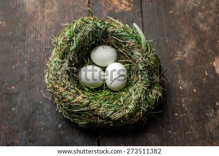 Organic white eggs in hay nest at wooden table. Eco food composition in rural vintage style - stock photo