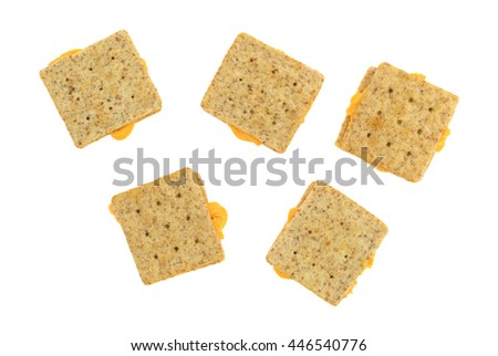 Organic whole wheat crackers with canned cheese between the crackers isolated on a white background. - stock photo