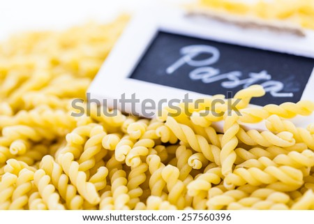 Organic yellow gemelli pasta on a white background.