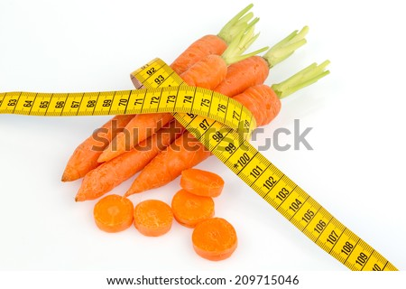 organically grown carrots with tape measure. fresh fruit and vegetables are always healthy. symbolic photo for a healthy diet. - stock photo