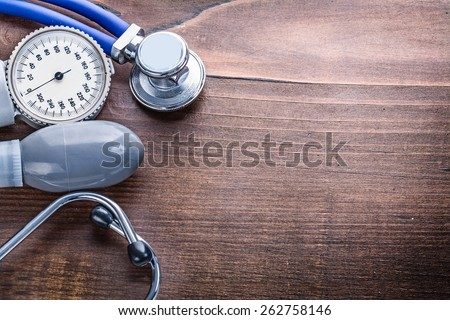 organized copyspace blood pressure monitor stethoscope on vintage wooden board medical concept  - stock photo