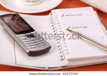 organizer and mobile phone on desk - stock photo