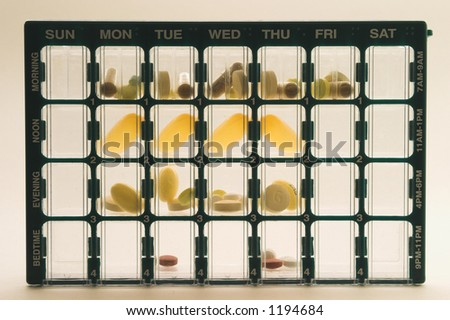 Organizer for medications with compartments for keeping track of daily doses of medicine over a week; upright, centered, fills the frame, lighted from behind making pills appear translucent - stock photo