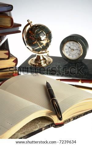 Organizer, pen, books, globe and a clock - stock photo
