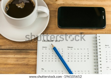 organizer with pencil, coffe cup and smart phone on wooden table, business concept - stock photo