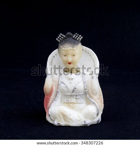 Oriental beauty - antique figurine from bone, full face. Background is black. - stock photo