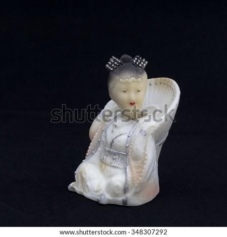 Oriental beauty - antique figurine from bone, half-turn. Background is black. - stock photo