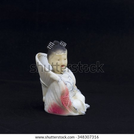 Oriental beauty -  antique figurine from bone, in a half-turn. Background is black. - stock photo