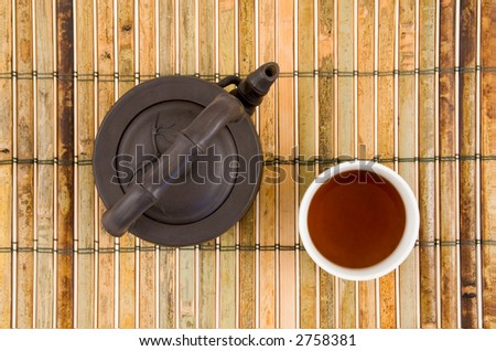Oriental Clay Teapot with Cup of Brewed Tea on Green Bamboo Background - stock photo