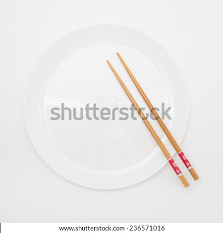 Oriental cutlery isolated on white background. White round plate and wooden sticks - stock photo