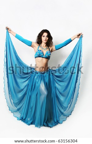 Oriental dancer Beautiful cabaret woman in blue dress. Attractive show girl in bright bra and long wide flared skirt.