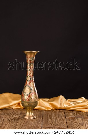 Oriental metal jar on wooden table. As a whole background. - stock photo