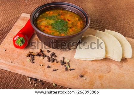 Oriental soup. Eastern food with different spices and bread on wood isolated on vintage background - stock photo