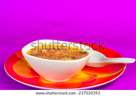 Oriental style soup bowl and spoon on bright red plate filled with spicy hot and sour soup against purple background. - stock photo