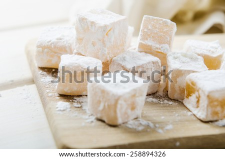 oriental sweets in powdered sugar on a wooden board - stock photo