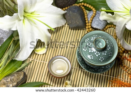 Oriental traditional tea ceremony still life - tea cups, beads, lily flowers, stones and bamboo leafs  on bamboo mat background. - stock photo