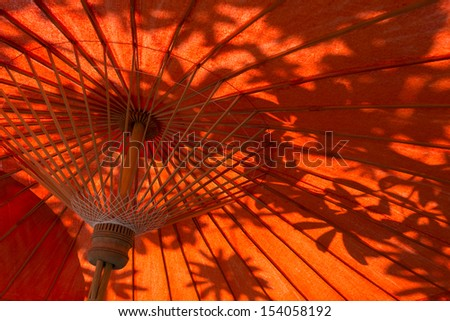 Oriental umbrellas and leaves shadow in Thailand - stock photo