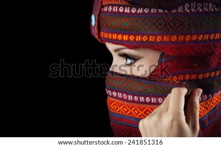 Oriental woman in turban covering her face on black background - stock photo
