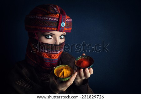 Oriental woman in turban offering red chili and yellow turmeric powders at bazar - stock photo