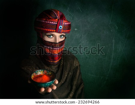 Oriental woman in turban offering red chili powder at green textured wall - stock photo