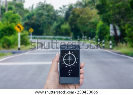 Orientation Concept a Hand Hold a Compass on smart phone  - stock photo