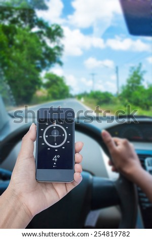 Orientation Concept a Hand Holding a Compass on smartphone in the car  - stock photo