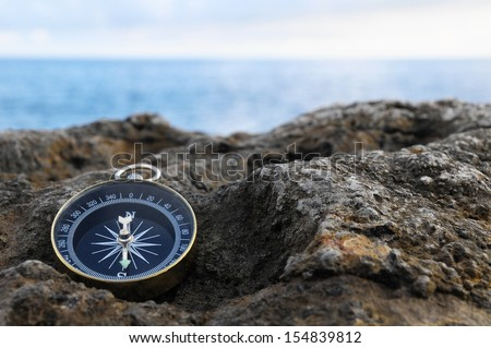 Orientation Concept - Analogical Compass Abandoned on the Rocks - stock photo