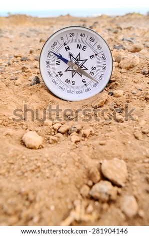 Orientation Concept Metal Compass on a Rock in the Desert - stock photo