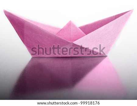 Origami a boat from the pink paper.