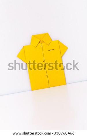 origami a man's shirt on a white background yellow of paper - stock photo
