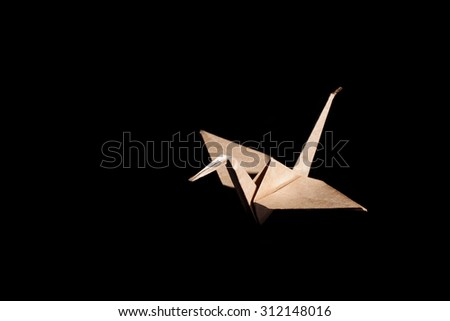 Origami bird made from brown recycle paper isolated on black background - stock photo