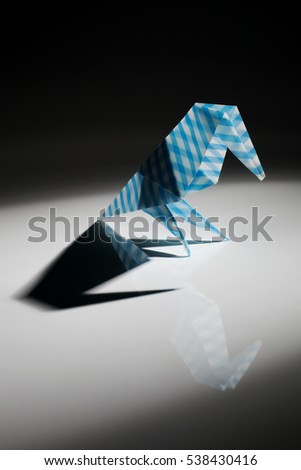 Origami bird made of blue paper isolated on black background
