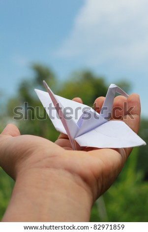 Origami bird on the hand with blue sky. - stock photo