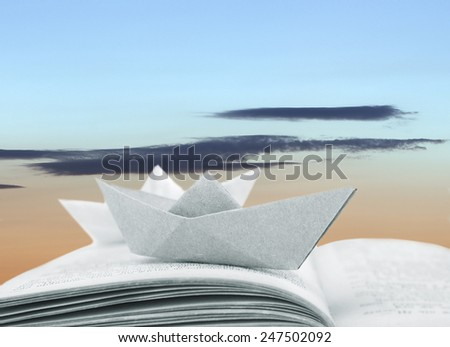 Origami boats on book on sky background