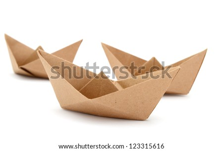 Origami brown paper ships on leading